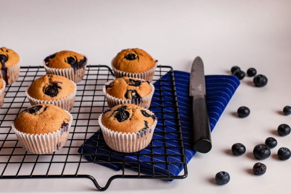 Blueberry muffins on a baking shelf.