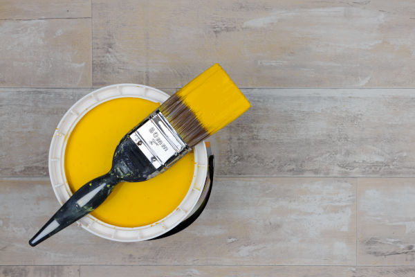 Paintbrush across an open can of bright yellow paint