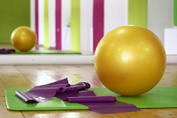 An exercise ball next to a yoga mat.
